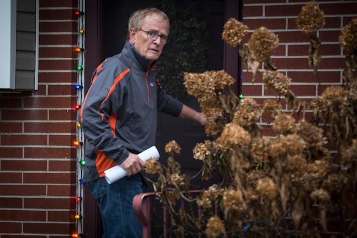 Muncie Mayor Dennis Tyler enters his home Monday afternoon after being arrested by the FBI. Tyler was indicted for theft of government funds.
