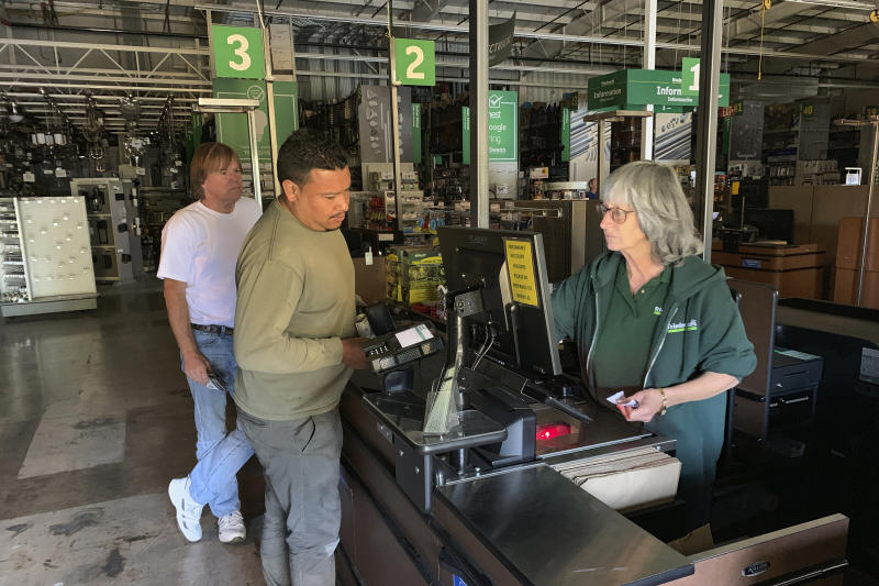 Cashier Lorna Pine, right, checks out customers at Sonoma's Friedman's Home Improvement, which remained open with limited electricity from a backup generator in Sonoma, Calif., Wednesday, Oct. 9, 2019. Employees escorted customers through the darkened store with flashlights and headlamps. Pacific Gas & Electric has cut power to more than half a million customers in Northern California hoping to prevent wildfires during dry, windy weather throughout the region. (AP Photo/Terry Chea)