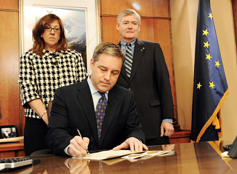 Alaska Gov. Sean Parnell, center, signs the certificate of election for U.S. Sen. Lisa Murkowski,R-Alaska, as the Director of the Division of Elections Gail Fenumiai, left, and Lt. Gov. Mead Treadwell watch, in Juneau, Alaska, Thursday, Dec. 30, 2010. The certificate will be hand delivered by Mrs. Fenumiai to the President of the Senate. (AP Photo/Chris Miller)