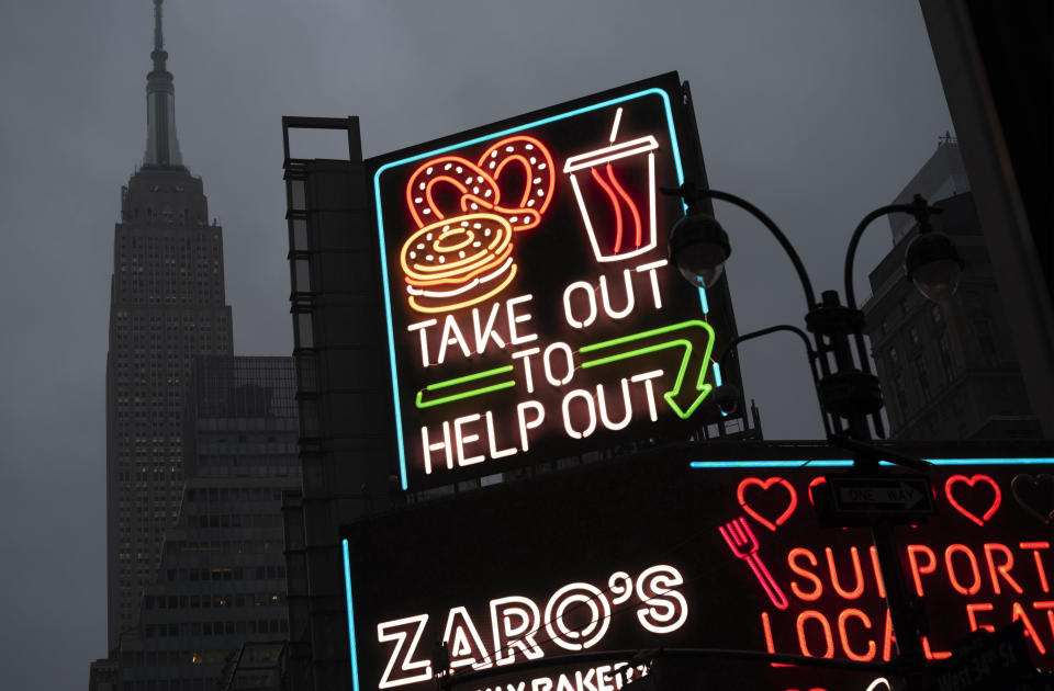 """A billboard in midtown Manhattan reads """"Take Out To Help Out, Monday, Nov. 30, 2020 in New York. (AP Photo/Mark Lennihan)"""