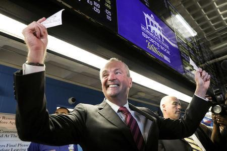 FILE PHOTO: New Jersey Governor Phil Murphy holds up his bet tickets after placing the first legal sports bets in the State of New Jersey at Monmouth Park Sports Book by William Hill, on the opening of the first day of legal betting on sports in Oceanport, New Jersey, U.S., June 14, 2018. REUTERS/Mike Segar/File Photo