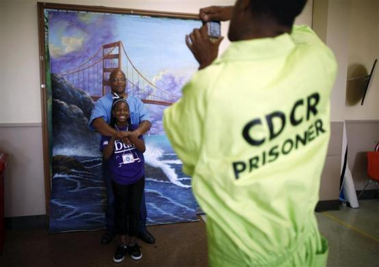 Troyanna, 10, hugs her father Troy, 49, as they have a picture taken in front of a backdrop of the Golden Gate Bridge, after meeting for the first time at San Quentin state prison in San Quentin, California June 8, 2012.
