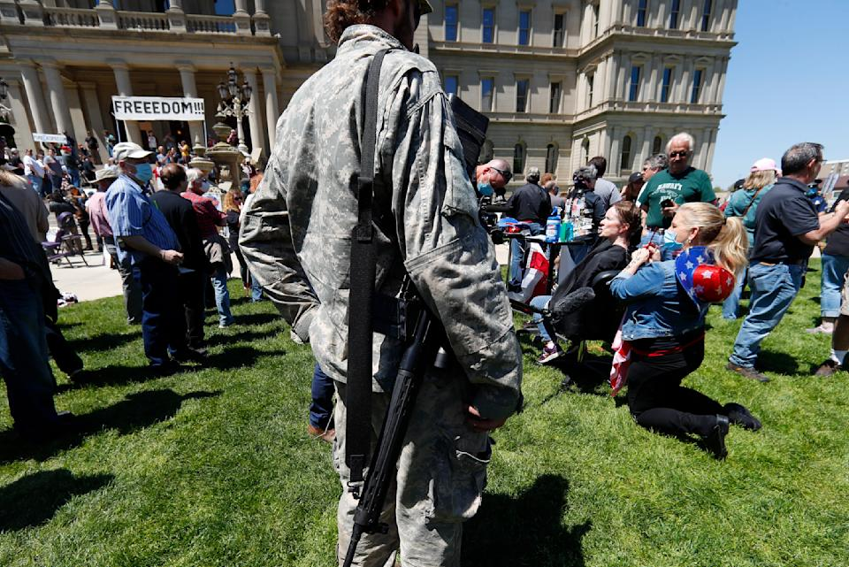 A protester with a rifle, left, watches Linda Hicks, seated, receive a free haircut from Teresa Luks, right, at the State Capitol during a rally in Lansing, Mich., Wednesday, May 20, 2020. Barbers and hair stylists are protesting the state's stay-at-home orders, a defiant demonstration that reflects how salons have become a symbol for small businesses that are eager to reopen two months after the COVID-19 pandemic began. (AP Photo/Paul Sancya)