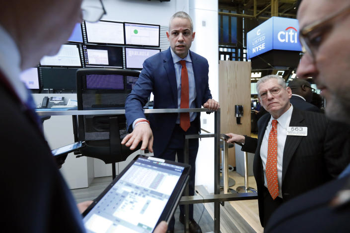 Director of Trading Floor Operations Fernando Munoz, center, works with the traders during a trading halt on the floor of the New York Stock Exchange, Monday, March 9, 2020. The Dow Jones Industrial Average plummeted 1,500 points, or 6%, following similar drops in Europe after a fight among major crude-producing countries jolted investors already on edge about the widening fallout from the outbreak of the new coronavirus. (AP Photo/Richard Drew)
