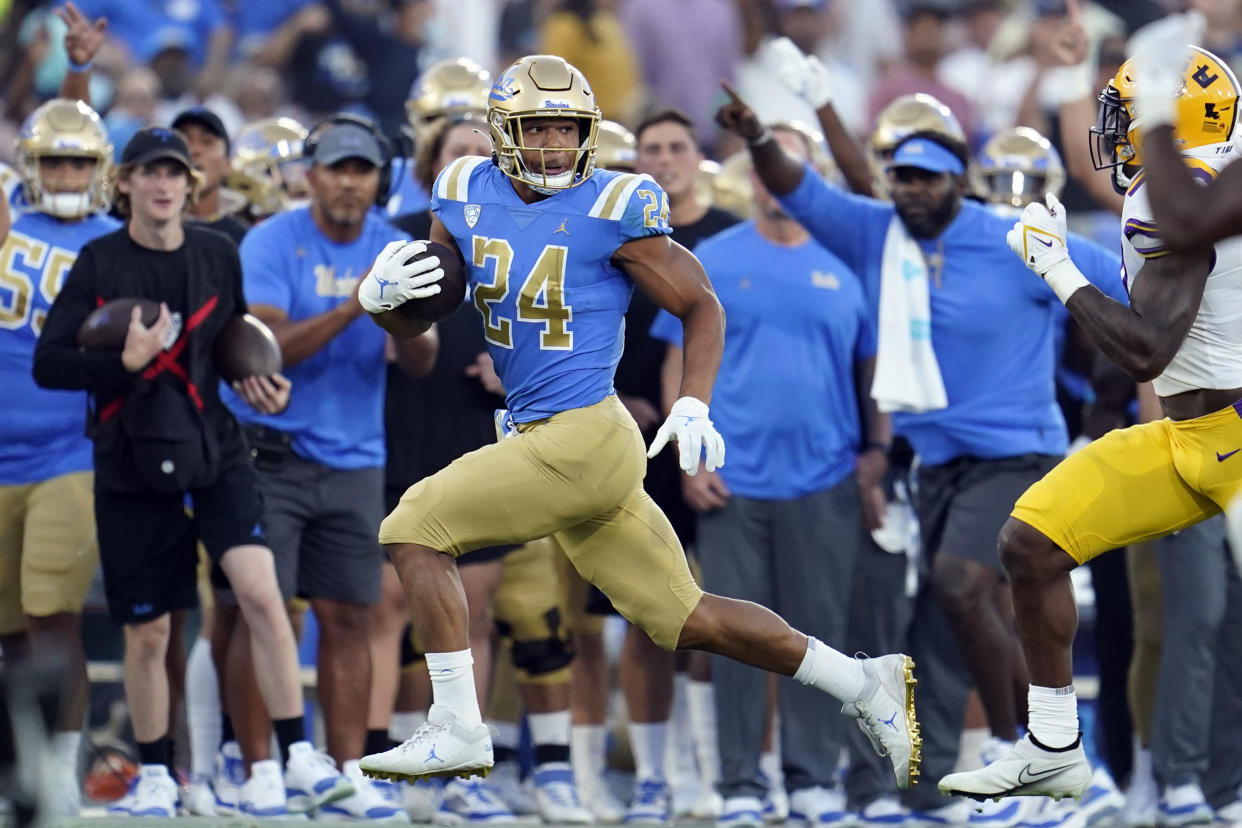 UCLA running back Zach Charbonnet (24) looks back at an LSU defender during the first half of an NCAA college football game Saturday, Sept. 4, 2021, in Pasadena, Calif. (AP Photo/Marcio Jose Sanchez)