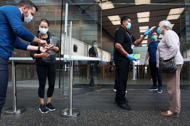 PHOTO: A customer has her temperature tested prior to entering the Apple Store at Bondi Junction on May 07, 2020, in Sydney. (Lisa Maree Williams/Getty Images)