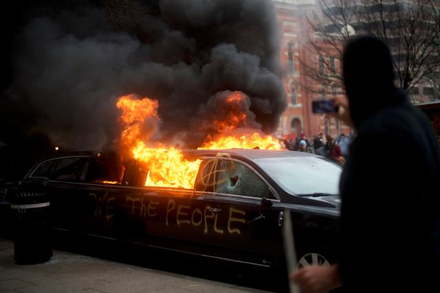 "A limousine with the graffiti of ""We the People"" spray-painted on the side is set ablaze."