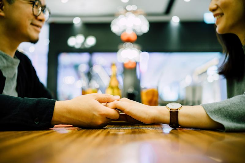 Young loving couple holding hands across a table during a dinner date at a restaurant
