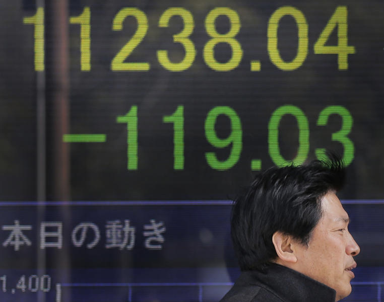 A man walks by the electronic stock board of a securities firm in Tokyo as Japan's Nikkei 225 dropped 119.03 points to 11,238.04 at one point Friday afternoon, Feb. 8, 2013, slumping after a recent rally spurred by a weakening yen. (AP Photo/Itsuo Inouye)