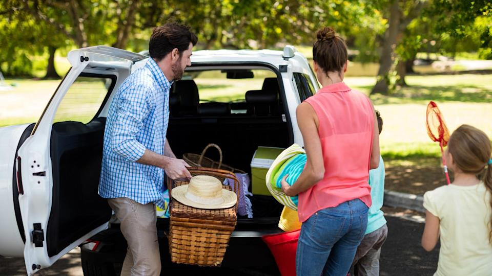 Family placing picnic items in car trunk at park.