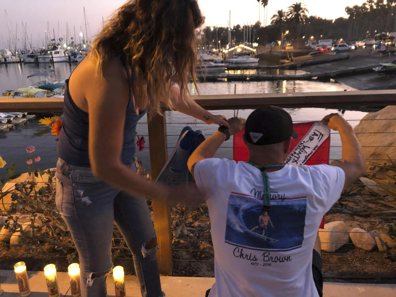 JJ Lambert, 38, and his fiancee, Jenna Marsala, 33, hang up a dive flag in remembrance of the victims of the Conception boat fire at a memorial site on Monday, Sept. 2, 2019, in Santa Barbara, Calif. (Photo: Stefanie Dazio/AP)