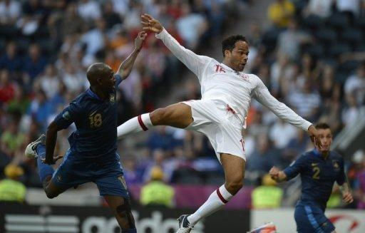 English defender Joleon Lescott (right) leaps above French midfielder Alou Diarra to score with a header during the Euro 2012 match at the Donbass Arena in Donetsk, Ukraine, on June 11. An experimental England held in-form France to a 1-1 draw on Monday as Roy Hodgson's patchwork side showed they have every intention of making an impact at Euro 2012