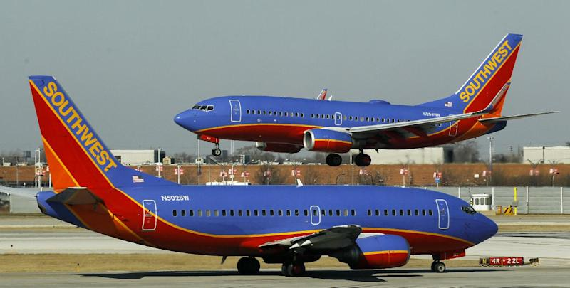 """FILE - In this Feb. 9, 2012 file photo, a Southwest Airlines Boeing 737 waits to take off at Chicago's Midway Airport as another lands. Southwest Airlines' attempt to thank its online friends with a half-price ticket sale has backfired with customers inadvertently being billed multiple times, not feeling the """"luv.""""  Airline spokeswoman Ashley Dillon on Saturday, Aug. 4, 2012 blamed a """"technology glitch"""" for the duplicate billings to debit and credit cards. (AP Photo/Charles Rex Arbogast, File)"""