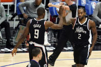 Los Angeles Clippers forward Kawhi Leonard (2) is high-fived by Serge Ibaka (9) after Leonard scored during the first half of the team's NBA basketball game against the Boston Celtics on Friday, Feb. 5, 2021, in Los Angeles. (AP Photo/Marcio Jose Sanchez)