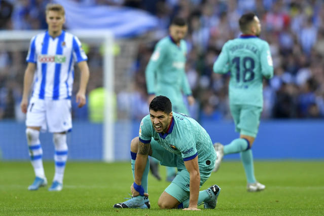 Barcelona's Luis Suarez grimaces while holding his ankle during the Spanish La Liga soccer match between Real Sociedad and Barcelona, at Anoeta stadium, in San Sebastian, Spain, Saturday, Dec. 14, 2019. (AP Photo/Alvaro Barrientos)