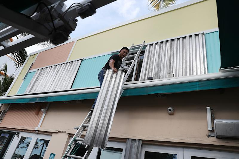 A man places a hurricane shutter over a window as he helps prepare a business for the possible arrival of Hurricane Dorian on August 30, 2019 in Miami Beach.(Photo: Joe Raedle/Getty Images)