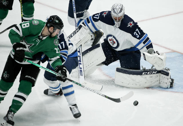 Dallas Stars forward Jason Dickinson (18) attempts a backhand shot as Winnipeg Jets forward Adam Lowry (17) and goaltender Connor Hellebuyck (37) defend during the second period of an NHL hockey game Thursday, Dec. 5, 2019, in Dallas. (AP Photo/Brandon Wade)
