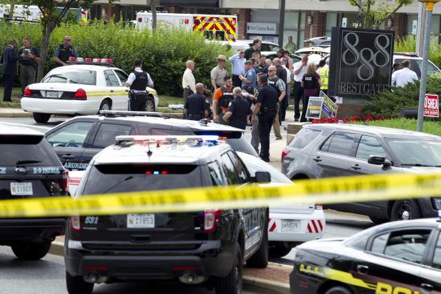 <p>Authorities stage at the office building entrance after multiple people were shot at The Capital Gazette newspaper in Annapolis, Md., Thursday, June 28, 2018. (Photo: Jose Luis Magana/AP) </p>
