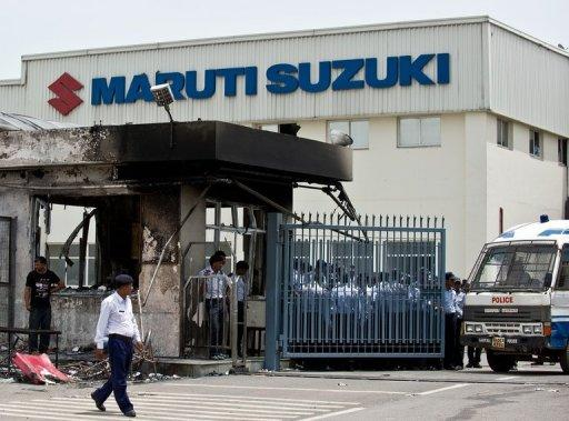 Indian private security guards stand behind the main gate of Maruti Suzuki Production Facility in Manesar
