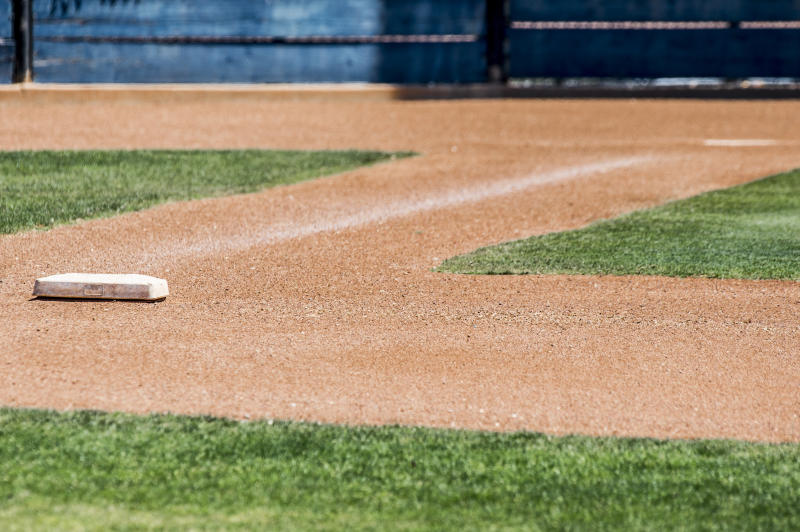 first base with home plate in background isolated on an empty baseball diamond