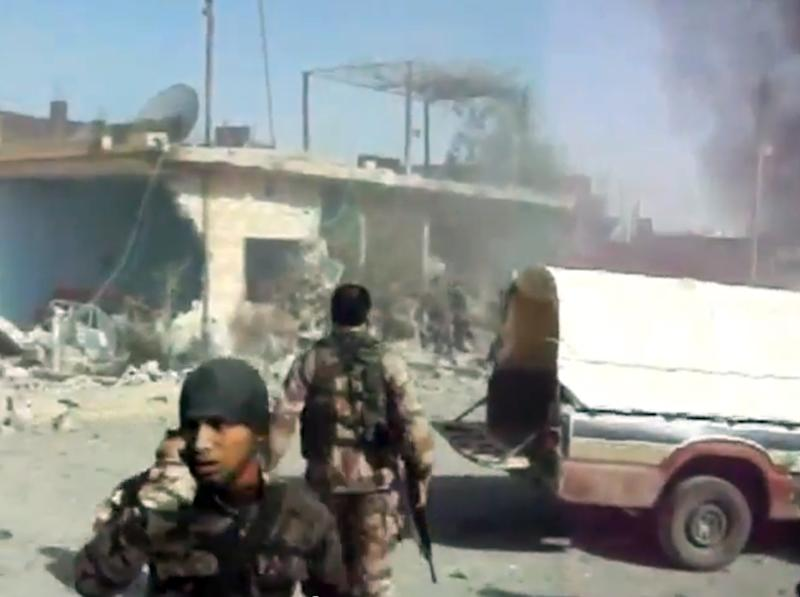 This image taken from video obtained from Shaam News Network, which has been authenticated based on its contents and an Associated Press journalist who saw a plane bomb an area around the Syrian-Turkish border town of Ras al-Ayn, shows Syrians rebels inspecting the damage moments after an airstrike by Syrian warplanes in Ras al-Ayn, Syria, Monday, Nov. 12, 2012. (AP Photo/Shaam News Network via AP video)