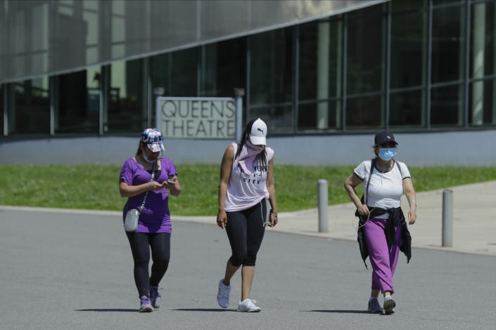 Women wear protective masks during the coronavirus pandemic as they pass the Queens Theatre, Tuesday, May 26, 2020, in the Queens borough of New York. (AP Photo/Frank Franklin II)