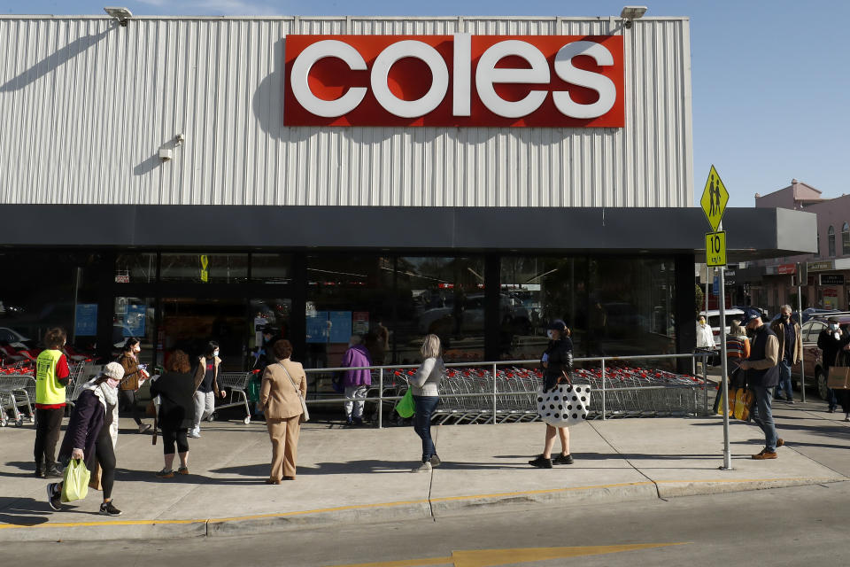 A controller monitors entry outside a Coles store. Source: Getty Images