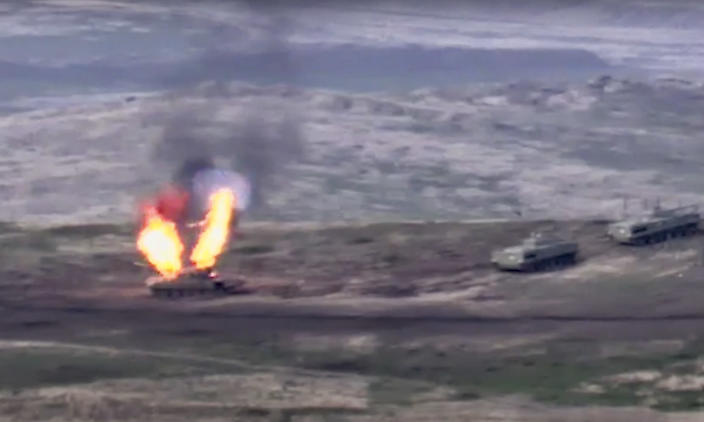 In this image taken from a footage released by Armenian Defense Ministry on Sunday, Sept. 27, 2020, Armenian forces destroy Azerbaijani tank at the contact line of the self-proclaimed Republic of Nagorno-Karabakh, Azerbaijan. Fighting between Armenia and Azerbaijan has broken out around the separatist region of Nagorno-Karabakh and the Armenian Defense Ministry says two Azerbaijani helicopters have been shot down. Ministry spokeswoman Shushan Stepanyan also said Armenian forces hit three Azerbaijani tanks. (Armenian Defense Ministry via AP)