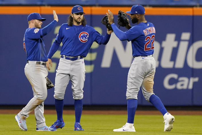 From left to right, Chicago Cubs outfielder Ian Happ, center fielder Jake Marisnick and right fielder Jayson Heyward celebrate after their victory over the New York Mets in a baseball game, Thursday, June 17, 2021, in New York. (AP Photo/Kathy Willens)