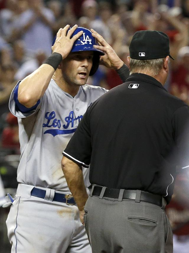 Los Angeles Dodgers' Michael Young, left, shows his disbelief after being called out on a play at home plate by umpire Joe West in the sixth inning during a baseball game against the Arizona Diamondbacks on Wednesday, Sept. 18, 2013, in Phoenix. (AP Photo/Ross D. Franklin)