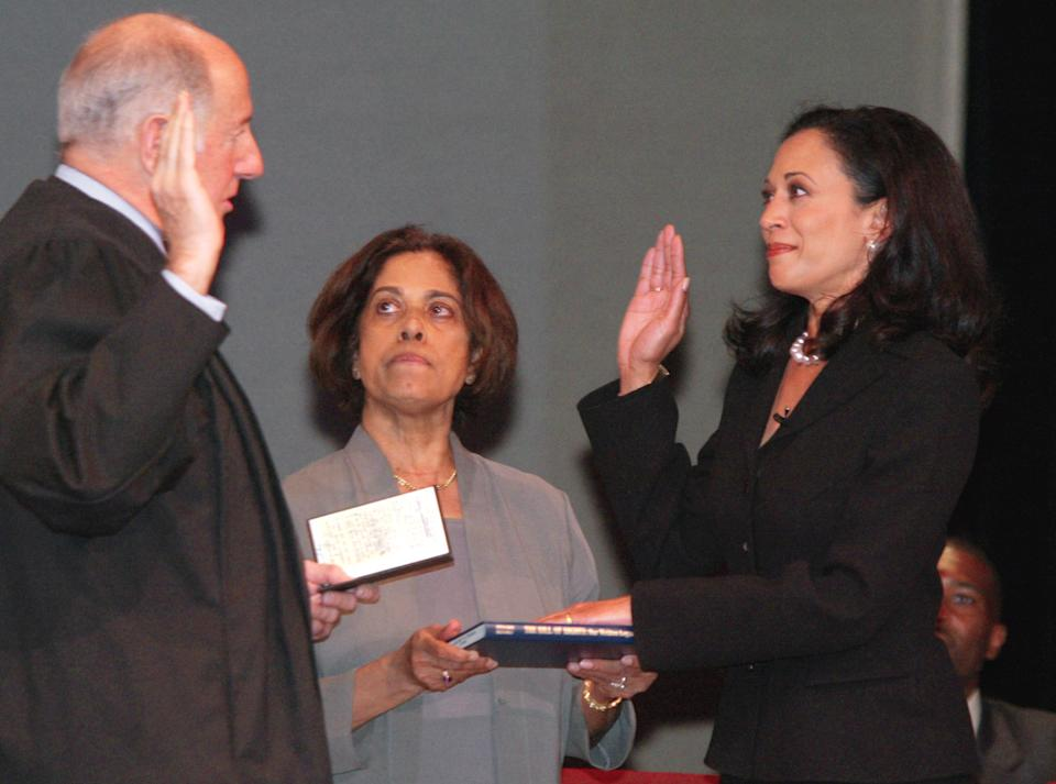 "San Francisco's new district attorney, Kamala Harris, right, receives the oath of office from California Supreme Court Chief Justice Ronald M. George, left, during inauguration ceremonies Thursday, Jan. 8, 2004, in San Francisco. In the center is Harris' mother, Dr. Shyamala Gopalan, who holds a copy of ""The Bill of Rights."" (George Nikitin/AP)"
