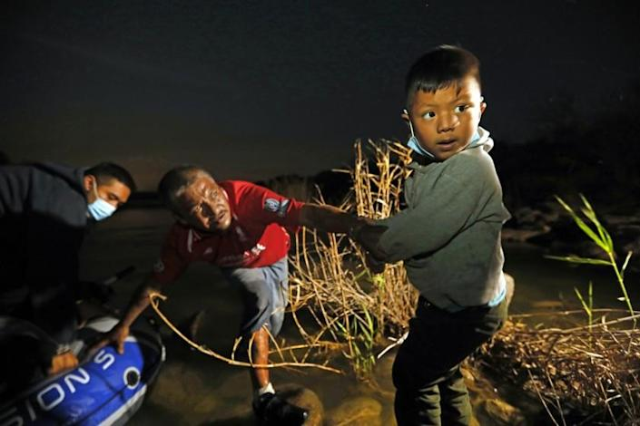 ROMA, TEXAS - ROMA, TEXAS - March 26, 2021—A young boy, Carlos, age 5, from El Salvador is placed on the rocks by a smuggler as his father Eddy, age 25, gets out of the raft after crossing the Rio Grande River on March 26, 2021. Migrants are smuggled across the Rio Grande River on their way to seek asylum in the United State. As hundreds of migrants cross the Rio Grande River in hopes of getting asylum, they leave behind all kinds of items as they journey north. Carolyn Cole / Los Angeles Times): Friday, March 26, 2021 in Roma, Texas.