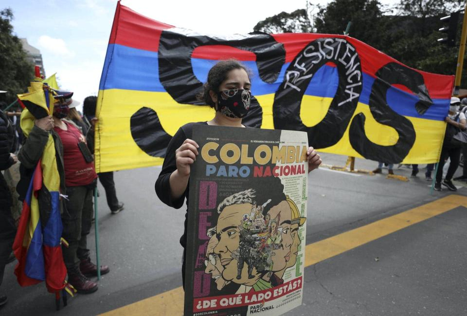 A woman protester holds a sign in front of the Colombian flag