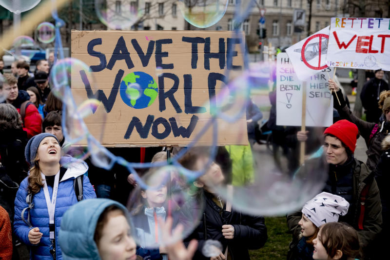 "Young people protest for climate action with a sign reading 'Save the World Now"" during a 'Friday for Future' demonstration in Berlin, Germany, Friday, March 22, 2019. (Christoph Soeder/dpa via AP)"