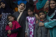 Wife and children wail near the coffin of elected official Riyaz Ahmad during his funeral in Sopore, 55 kilometers (34 miles) north of Srinagar, Indian controlled Kashmir, Monday, March. 29, 2021. Gunmen killed an elected official of India's ruling party and a policeman in disputed Kashmir on Monday, police said. Police blamed anti-India militants for the attack. None of the rebel groups that have been fighting against Indian rule since 1989 immediately claimed responsibility for the attack. (AP Photo/Mukhtar Khan).
