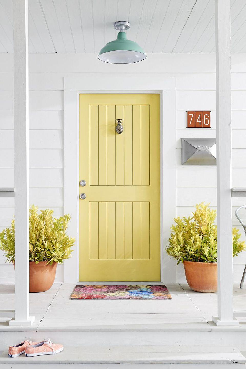 """<p>A yellow door is guaranteed to put a smile on the face of anyone who walks through it. Pair it with a minty overhead light for a retro vibe.</p><p><a class=""""link rapid-noclick-resp"""" href=""""https://www.sherwin-williams.com/homeowners/products/interior-paint-coatings/interior-paint?selectedColorNumber=SW6908"""" rel=""""nofollow noopener"""" target=""""_blank"""" data-ylk=""""slk:SHOP YELLOW PAINT"""">SHOP YELLOW PAINT</a></p>"""