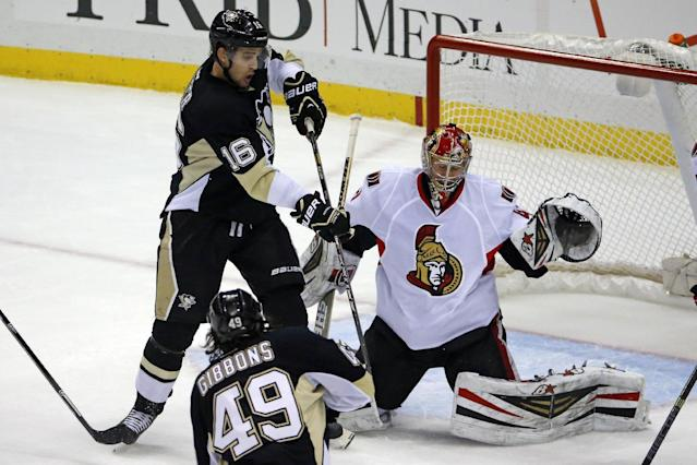 Pittsburgh Penguins' Brian Gibbons (49) deflects the puck between the pads of Ottawa Senators goalie Craig Anderson (41) in the first period of an NHL hockey game between the Pittsburgh Penguins and the Ottawa Senators in Pittsburgh, Monday, Feb. 3, 2014. (AP Photo/Gene J. Puskar)