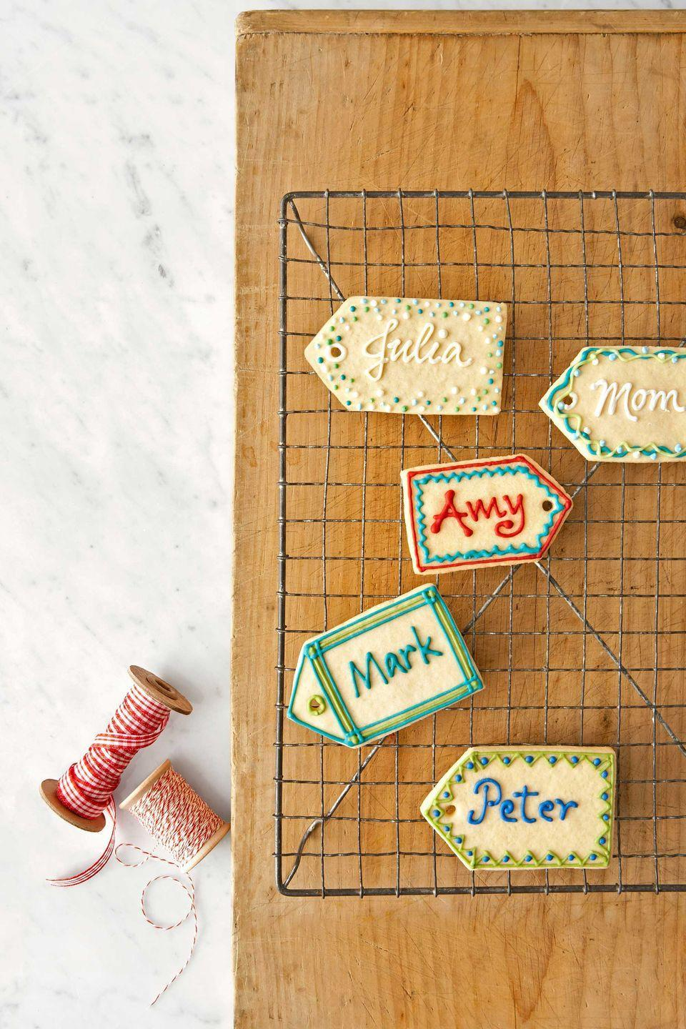 "<p>To create these sweet name tags, follow our recipe for sugar cookie dough. Form the cookies with a tag-shaped cutter, then use a plastic straw to punch a hole in the pointed end of each treat before baking.</p><p><a href=""https://www.countryliving.com/food-drinks/recipes/a3270/sugar-cookies-recipe/"" rel=""nofollow noopener"" target=""_blank"" data-ylk=""slk:Get the recipe."" class=""link rapid-noclick-resp""><strong>Get the recipe.</strong></a></p>"