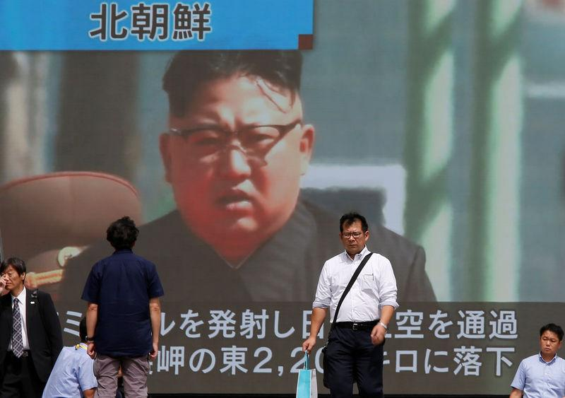 Passersby walk past a TV screen reporting news about North Korea's missile launch in Tokyo
