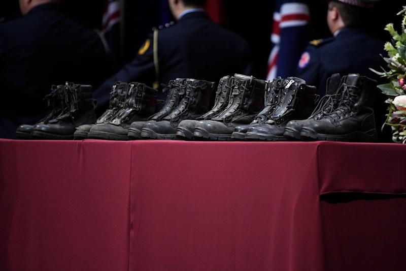 Fire boots representing the six RFS and Coulson Aviation firefighters killed in the recent bush fire are placed on stage during the Bushfire State Memorial at Qudos Bank Arena in Sydney, Sunday, February 23, 2020. (AAP Image/Bianca De Marchi) NO ARCHIVING