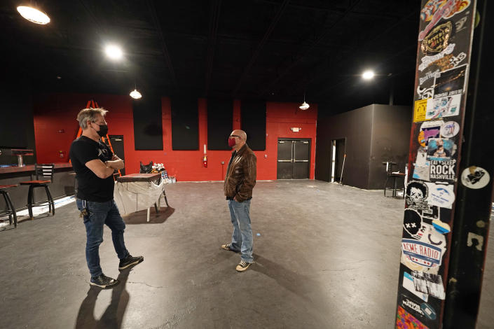 Mike Grimes, left, and Dave Brown, co-owners of The Basement East, talk inside the rebuilt music venue Thursday, Feb. 25, 2021, in Nashville, Tenn. The building was destroyed by a tornado March 3, 2020, and the difficulties of reopening were compounded by COVID-19. Now, as the anniversary of the two catastrophic events approaches, the owners hope to reopen their doors, this time with masks and tables spread out throughout their 5,000 square foot space. Amid signs that the virus is slowing its spread and more people are getting vaccines, they've set their sights on spring. (AP Photo/Mark Humphrey)