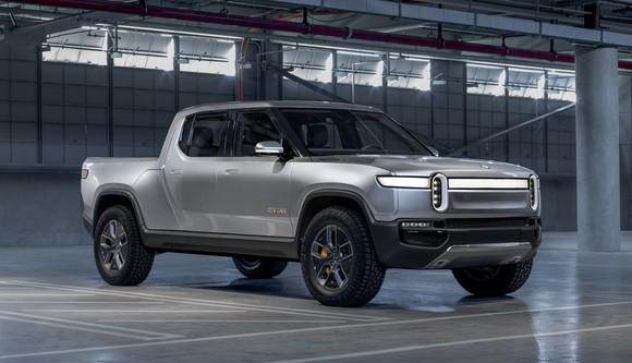 A silver Rivian R1T, a futuristic-looking pickup truck, shown in a garage.