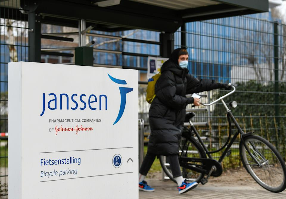 A woman leaves with her bike at Johnson and Johnson's subsidiary Janssen Vaccines in Leiden, Netherlands March 9, 2021. REUTERS/Piroschka van de Wouw