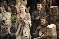 <p>It's not long before Sansa is embracing the style and color palate of King's Landing, but let's not ignore that rose-embroidered neckline, which might just have foreshadowed the protective role the Tyrells would play in Sansa's life after her father (Ned, sitting on the right) died. </p>