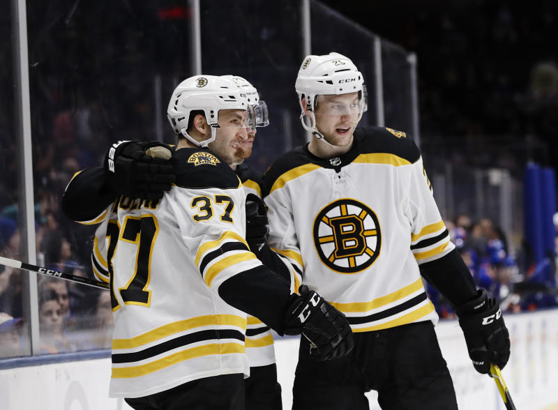 Boston Bruins' Patrice Bergeron, left, and teammate Brandon Carlo, right, celebrate with teammates after Bergeron scored a goal during the third period of an NHL hockey game against the New York Islanders Tuesday, March 19, 2019, in Uniondale, N.Y. The Bruins won 5-0. (AP Photo/Frank Franklin II)
