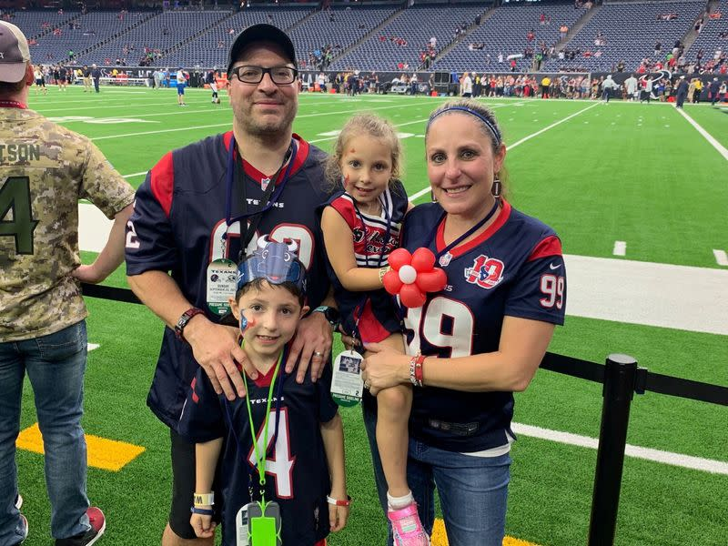 United Airlines flight attendants Rene and Jessica Trujillo pose with their children at NRG Stadium in Houston