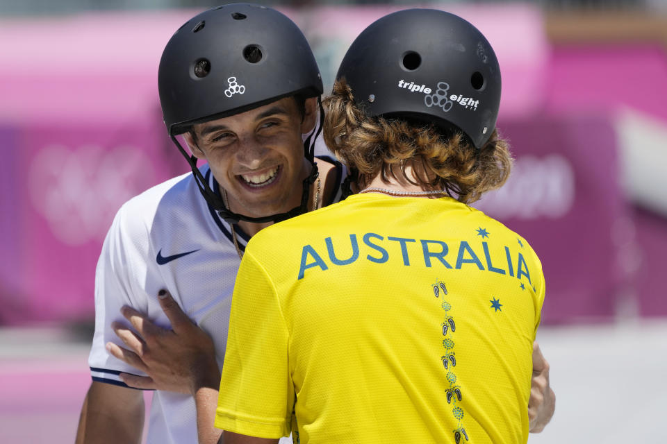 Keegan Palmer of Australia, right, embraces Cory Juneau of the United States during the men's park skateboarding finals at the 2020 Summer Olympics, Thursday, Aug. 5, 2021, in Tokyo, Japan. (AP Photo/Ben Curtis)