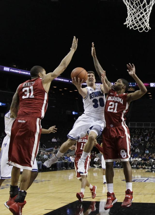 Seton Hall's Jaren Sina (30) drives past Oklahoma's Cameron Clark (21) during the first half of a Coaches vs. Cancer NCAA college basketball game on Friday, Nov. 22, 2013, in New York. (AP Photo/Frank Franklin II)