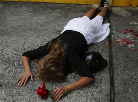 Carmen Gonzalez lies on the spot where her son Jimmy Vargas, a student, was injured at a protest, during his funeral in San Cristobal, about 410 miles (660 km) southwest of Caracas, February 26, 2014. REUTERS/Carlos Garcia Rawlins