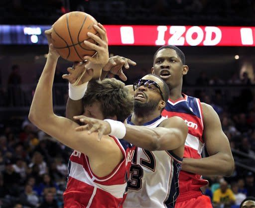 New Jersey Nets' Shelden Williams (33), center, grabs at the the ball with Washington Wizards' Jan Vesely, left, of Czech Republic, and Kevin Seraphin, right, of France, during the first quarter of an NBA basketball game in Newark, N.J., Friday, April 6, 2012. (AP Photo/Mel Evans)